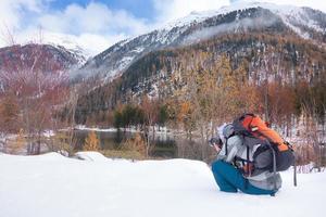 Fotógrafo en la nieve en otoño frente a un lago de montaña foto