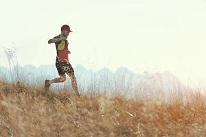 El hombre corre cuesta abajo entre los prados de las montañas otoñales. foto