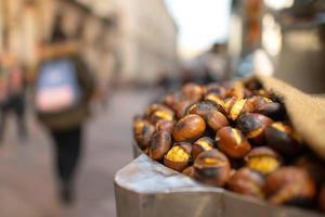 Castañas asadas a la venta en la calle de la ciudad en el otoño foto