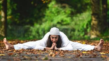 postura de yoga en el suelo en las hojas de otoño foto
