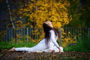 mujer joven, en, posición yoga, en el parque foto
