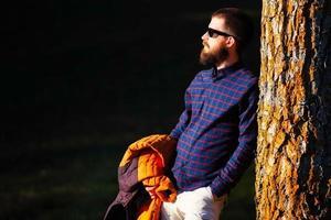 joven con barba descansando sobre una planta foto