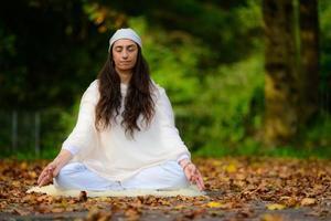 práctica de yoga en el parque de otoño por una niña foto