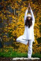 Mujer joven durante una práctica de yoga en la naturaleza de otoño foto