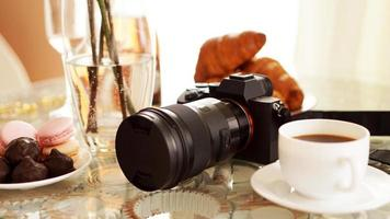 Photo camera with a lens on glass table. Cup of coffee