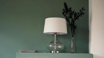 Lámpara de pie blanca y jarrón sobre fondo verde foto