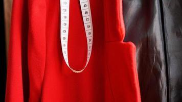 cinta métrica blanca sobre el fondo de la tela roja foto