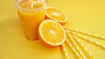 Jugo de naranja en comida rápida taza cerrada con tubo sobre fondo amarillo foto