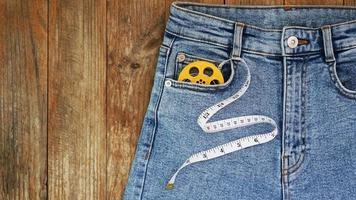 jeans azules y una cinta métrica. concepto de mezclilla para adelgazar o coser foto