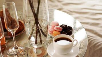 Glass table with a cup of coffee, sweet macaroons. photo