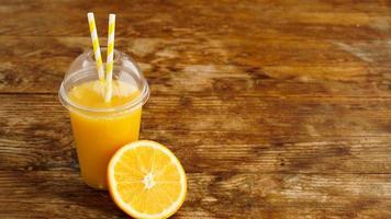 Jugo de naranja en comida rápida taza cerrada con tubos sobre mesa de madera foto