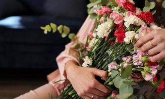 Woman holding a beautiful colourful blossoming flower bouquet photo