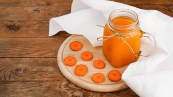 Jugo de zanahoria naranja brillante en un frasco de vidrio sobre un fondo de madera foto