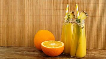 Two bottles of tropical juice with paper straws. Oranges and pineapple photo