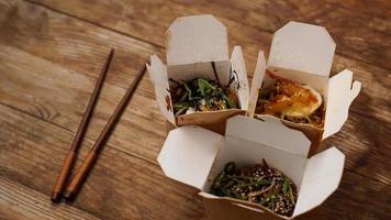 Fideos con carne de cerdo y verduras en caja para llevar sobre mesa de madera foto