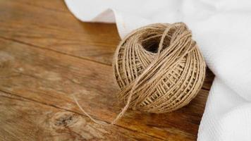 Madejas de cuerda de yute en la mesa de madera de fondo plano laico foto
