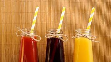 Tres bebidas multicolores en las botellas sobre un fondo de bambú de madera foto