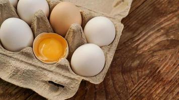 Cartón de huevos blancos y la mitad del huevo agrietado con vista superior de la yema foto