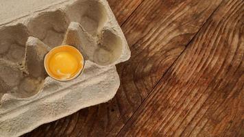 One broken egg in a cardboard egg tray. Half egg photo