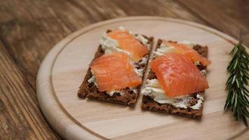 Sándwiches de salmón sobre tabla de cortar de madera foto