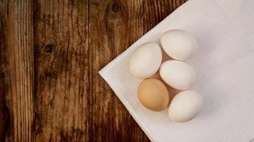 Cerca de huevos de gallina frescos en la mesa de madera de la naturaleza foto