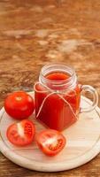 vaso de jugo de tomate en la mesa de madera. jugo de tomate fresco foto