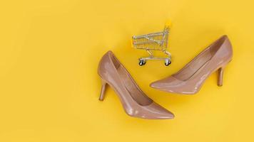 zapatos beige y un carrito de compras sobre un fondo amarillo. foto