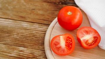 Whole and cut tomato on a wooden board for slicing photo