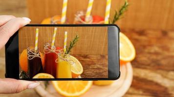 Mujer tomando foto de jugo de frutas en su teléfono inteligente