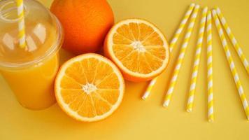 Jugo de naranja en taza cerrada de comida rápida con tubo en amarillo foto