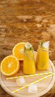 Orange juice on a wooden tray. Sliced orange and ice cubes photo