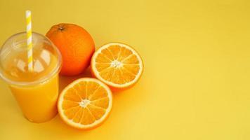 jugo de naranja en un vaso de plástico con una pajita. naranja en rodajas foto