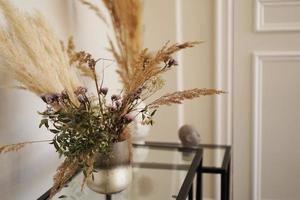 lindas flores secas en un pequeño jarrón de vidrio en la sala de estar foto