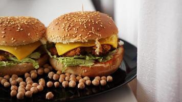 hamburguesa de verduras con chuleta de garbanzos. dos hamburguesas en plato negro foto