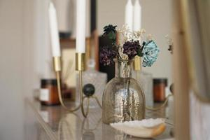 Home interior decor. Glass jar with dried flowers, vase and candle photo