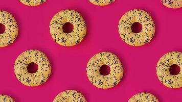 patrón creativo festivo de filas de donas sobre fondo rosa foto