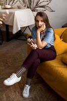 Artista de maquillaje con pinceles sentado en el sofá foto