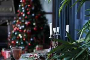 Metal candlestick with a white candle against the festive background photo