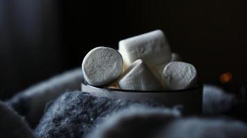 Hot cocoa with marshmallow in a white ceramic mug - dark background photo