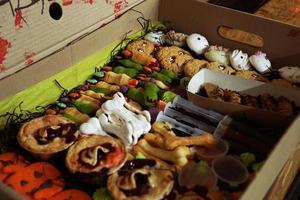 Set of festive Halloween cupcakes and treats and candy in a box photo