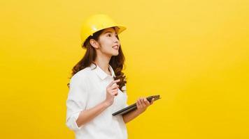 Ingeniero de mujer asiática con tableta digital sobre fondo amarillo. foto