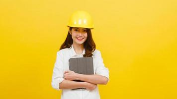 Asian woman engineer using digital tablet over yellow background. photo