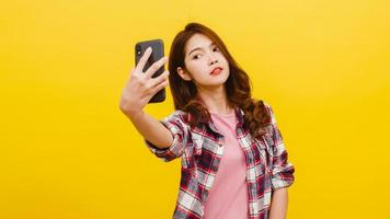 Asian female making selfie photo on phone with positive expression.