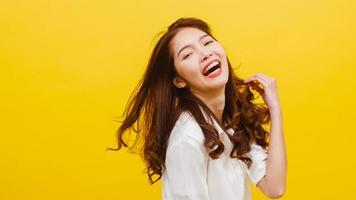 Young Asian lady listening to music and dancing on yellow background. photo