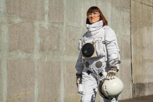 Woman astronaut without a helmet on the background of a gray wall photo
