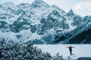 Woman in a poncho in the mountains in winter, adventure and travel photo