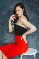 Beautiful young woman with glass of wine on gray background photo