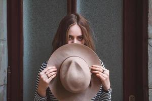 hermosa mujer en una camisa a rayas sosteniendo su sombrero foto