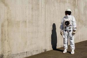 Futuristic astronaut in a helmet against gray walls photo
