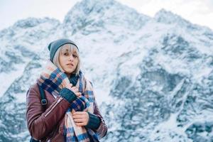Portrait of girl in a hat with a scarf in the mountains in winter photo